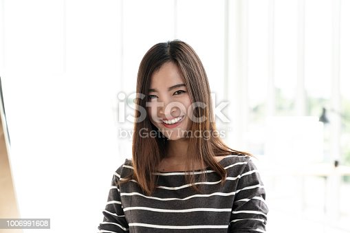 istock Portrait of young attractive asian creative woman or designer smiling and looking at camera in modern office feeling confident in casual outfit. Headshot of female employee, entrepreneur or student. 1006991608