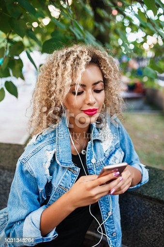 625928750 istock photo Portrait of young attractive black girl in urban background hearing music with headphones 1031348264