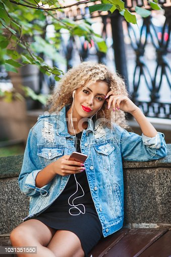 625928750 istock photo Portrait of young attractive black girl in urban background hearing music with headphones 1031351550
