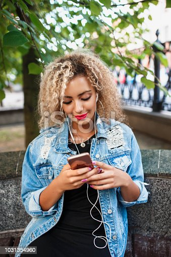 625928750 istock photo Portrait of young attractive black girl in urban background hearing music with headphones 1031354960