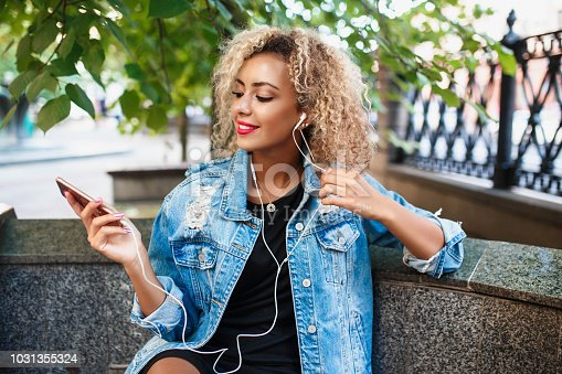625928750 istock photo Portrait of young attractive black girl in urban background hearing music with headphones 1031355324