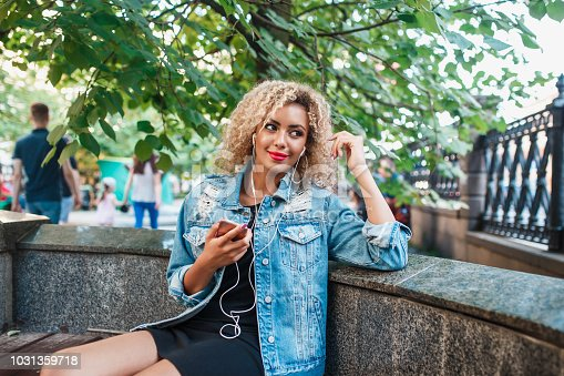 625928750 istock photo Portrait of young attractive black girl in urban background hearing music with headphones 1031359718