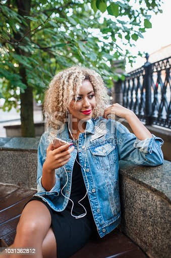 625928750 istock photo Portrait of young attractive black girl in urban background hearing music with headphones 1031362812