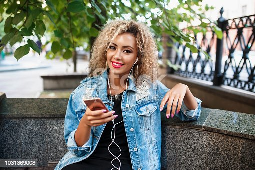 625928750 istock photo Portrait of young attractive black girl in urban background hearing music with headphones 1031369008