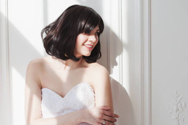 Portrait of young attractive brunette with short hair in a wedding dress. She is standing at the white walls, free space on the right. Joyful bride. stock photo