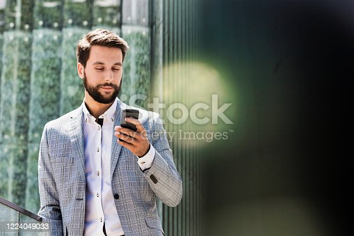 Portrait of young attractive businessman using smartphone