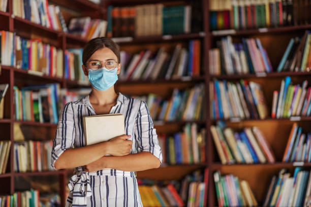 Portrait of young attractive college girl standing in library with face mask on holding a book. Studying during corona virus concept. stock photo