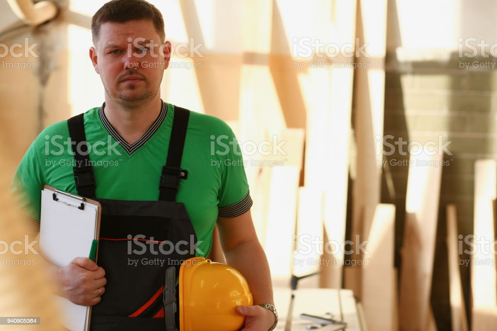 Portrait of young attractive man in work clothes and yellow helmet...