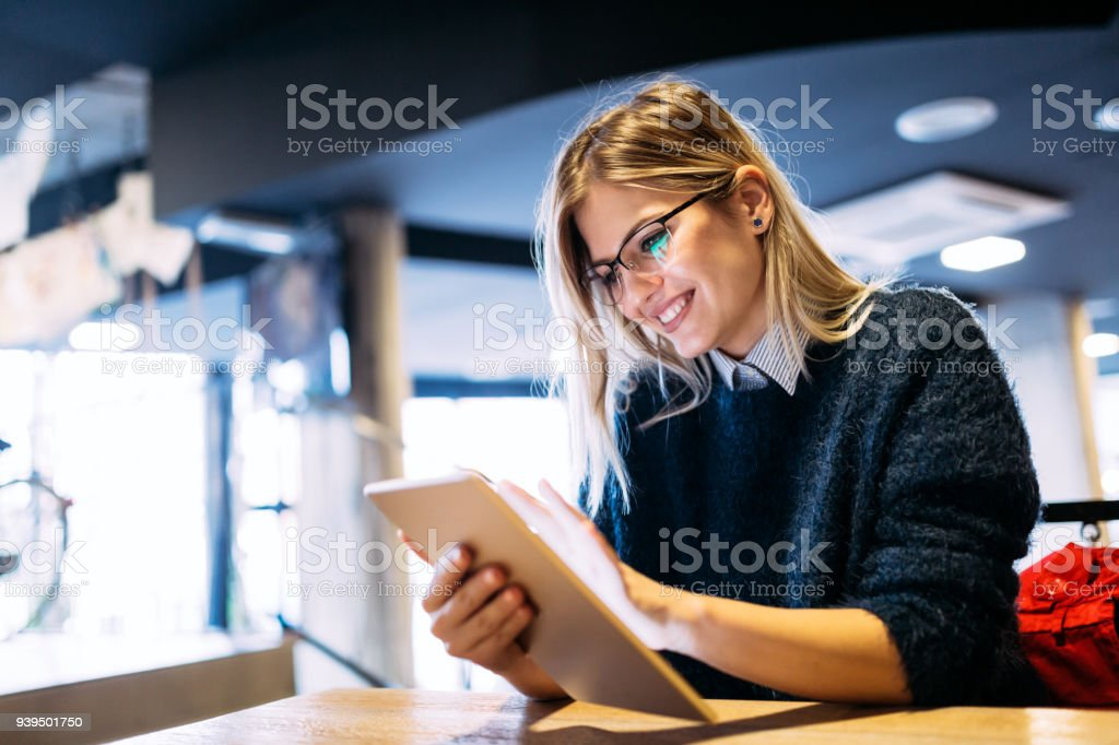 Portrait of young attractive woman using tablet stock photo