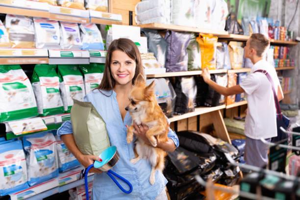 Porträt von jungen attraktiven Frau mit kleinem Hund in den Händen Kauf von Trockenfutter in Tierbedarfsgeschäft – Foto