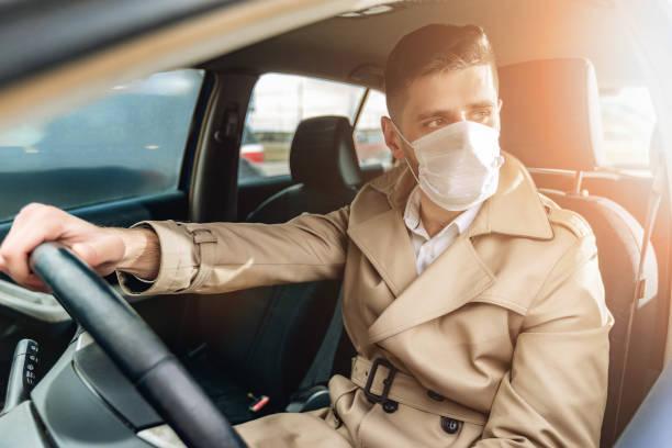 Porträt eines jungen bärtigen Mannes auf der Straße. Lifestyle-Konzept mit hübschen Kerl in einem Auto, die medizinische Gesichtsmaske verwenden – Foto