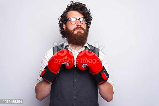 Portrait of young bearded man in suit with boxing gloves.