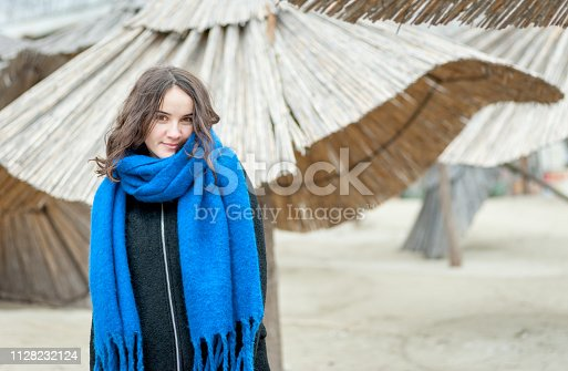 istock Portrait of young beautiful and cute girl in black coat and blue scarf outdoors on the cold weather with reed sunshades in the background 1128232124