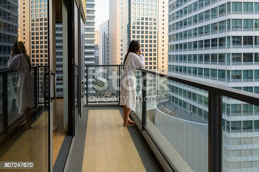 Portrait of young beautiful Asian woman enjoying the view of the city from the balcony horizontal shot