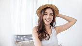 白い寝室で休暇の夏の時間に若い美しいアジアの女性の肖像画。夏の幸せな陽気な女の子。韓国メイクスキンケア。大学女性ファッションライフスタイルの概念.