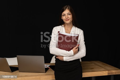 Portrait of young beautiful business woman worker looking away, holding folder in hands. Table withlaptops on background