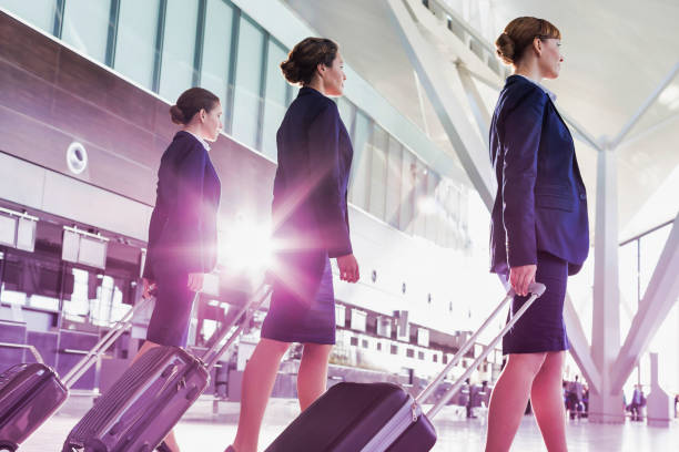 Portrait of young beautiful confident flight attendants walking in airport stock photo