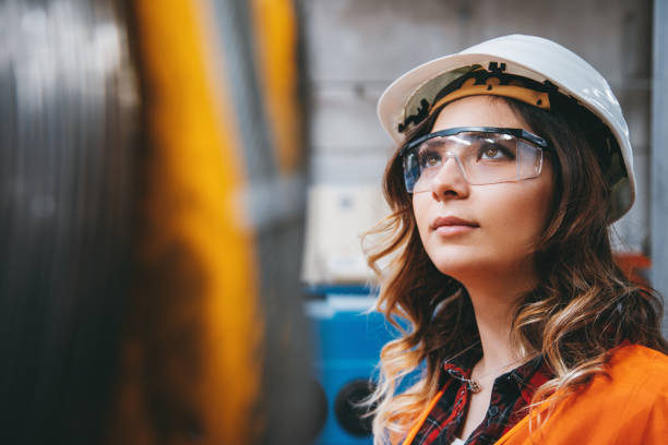 Portrait of young beautiful engineer woman working in factory building. Portrait of young businesswoman with white helmet looking up and seen from the industrial steel cable reel for crane in factory warehouse. She is testing and working with winding wire and cable drum accessories metal wire spool reel wear resistance. engineer stock pictures, royalty-free photos & images