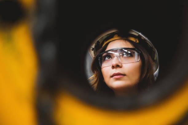 portret van jonge mooie ingenieur vrouw die werkt in fabrieksgebouw. - groothoek stockfoto's en -beelden