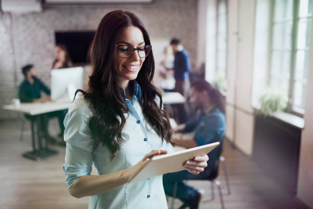 Portrait of young beautiful female designer using tablet stock photo