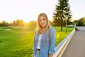 Portrait of young beautiful happy woman 19, 20 years old. Caucasian female in denim shirt smiling, looking at camera. Sunset, park, grass, road background