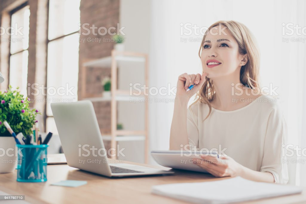 Portrait of young beautiful thoughtful lady sitting at the table working with laptop on writing down new ideas Portrait of young beautiful thoughtful lady sitting at the table working with laptop on writing down new ideas Adult Stock Photo