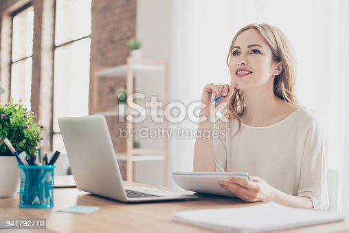 Portrait of young beautiful thoughtful lady sitting at the table working with laptop on writing down new ideas