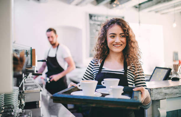Portrait of young beautiful waitress with a tray in a cafe, a man barista in the background. stock photo