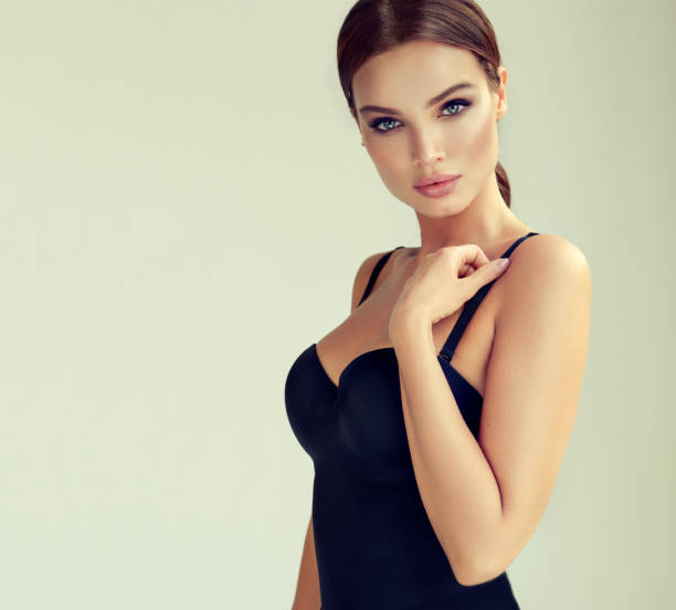Portrait of young, beautiful woman dressed in seductive black body. Makeup and cosmetology. stock photo