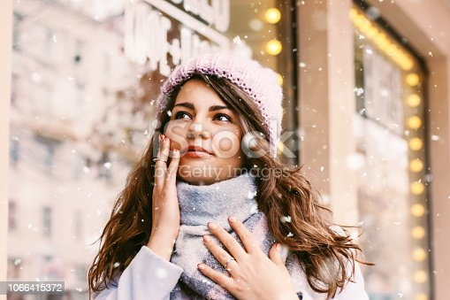 istock Portrait of young beautiful woman in coat and hat enjoing the fi 1066415372