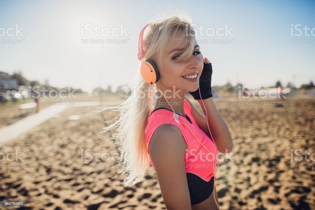 Portrait of young beautiful woman listening to music at beach. Close...