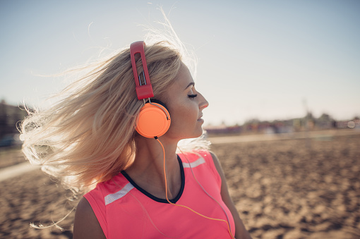 Portrait Of Young Beautiful Woman Listening To Music At Beach Close Up Face Of Smiling Blonde Woman With Earphone Looking At Camera Girl Running At Beach And Listening To Music Stock Photo - Download Image Now