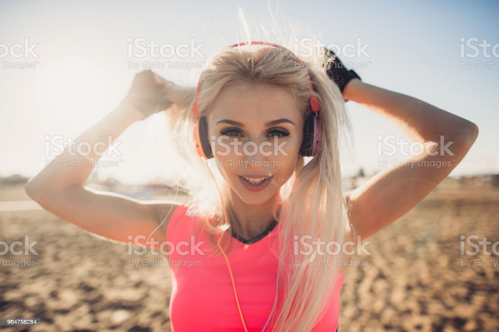 Portrait of young beautiful woman listening to music at beach. Close up face of smiling blonde woman with earphone looking at camera. Girl running at beach and listening to music royalty-free stock photo