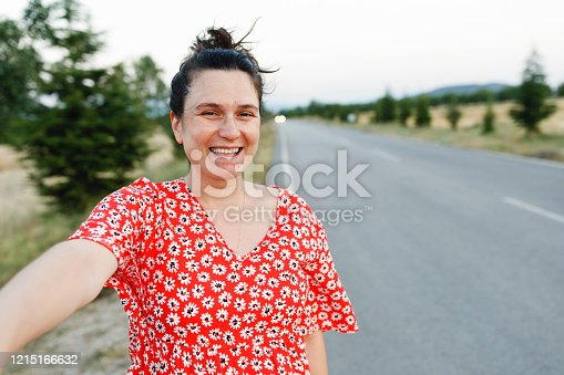 886858224 istock photo Portrait of young beautiful woman next to high way 1215166632