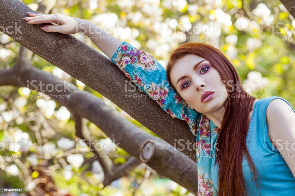 Portrait of young beautiful woman posing among blooming trees with pink eyeshadow. stock photo