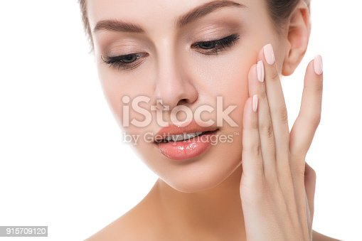 istock Portrait of young beautiful woman touching her face 915709120