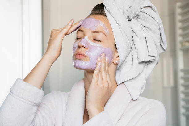 Portrait of young beautiful woman with a facial mask having a spa treatment at home stock photo