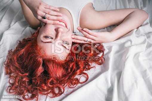 istock Portrait of young beautiful woman with long hair lying in the bed 646589140