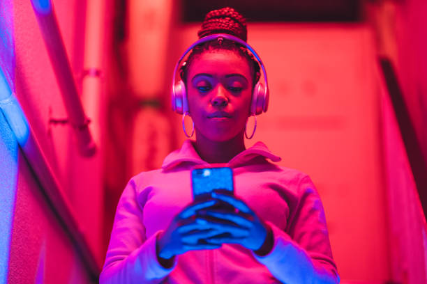 Portrait of young black woman listening to music under neon lights A portrait of a young black woman while she is listening to music under neon lights. bluetooth stock pictures, royalty-free photos & images