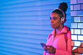 Portrait of young black woman listening to music under neon lights