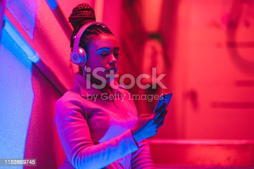 A portrait of a young black woman while she is listening to music under neon lights.