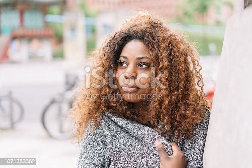 istock Portrait of young black woman wearing grey sweater 1071383362