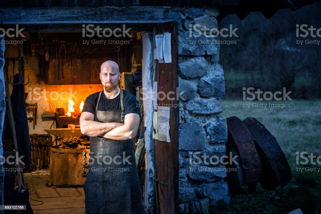 Portrait Of Young Blacksmith Standing In Front Of His Workshop stock photo