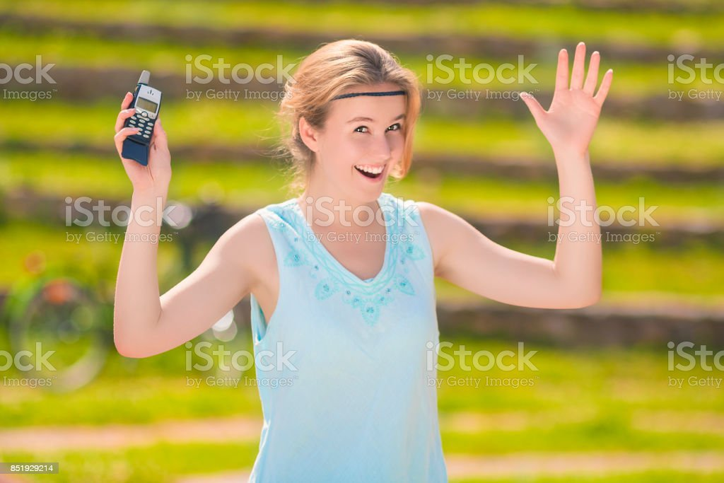 Portrait of Young Blond Caucasian Woman with Positive Expression Using Cellphone stock photo
