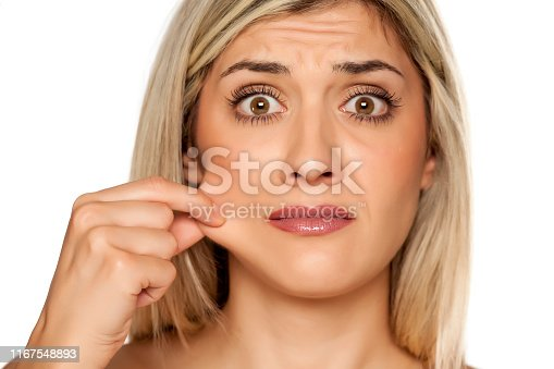 Portrait of young blond woman, pulling her cheek on white background