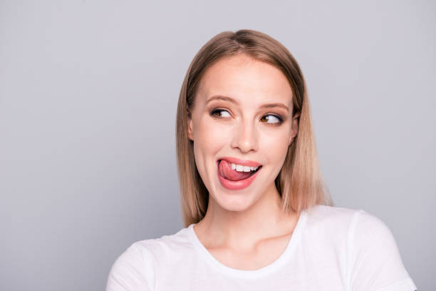 Portrait of young blonde gorgeous caucasian charming girl showing tongue out. Isolated over grey background stock photo