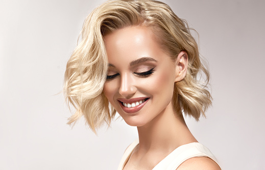 Portrait of beautifully looking young blonde middle length haired woman,dressed in a delicate evening makeup.Perfect model looking down. Beauty, elegance, hairstyling and cosmetic