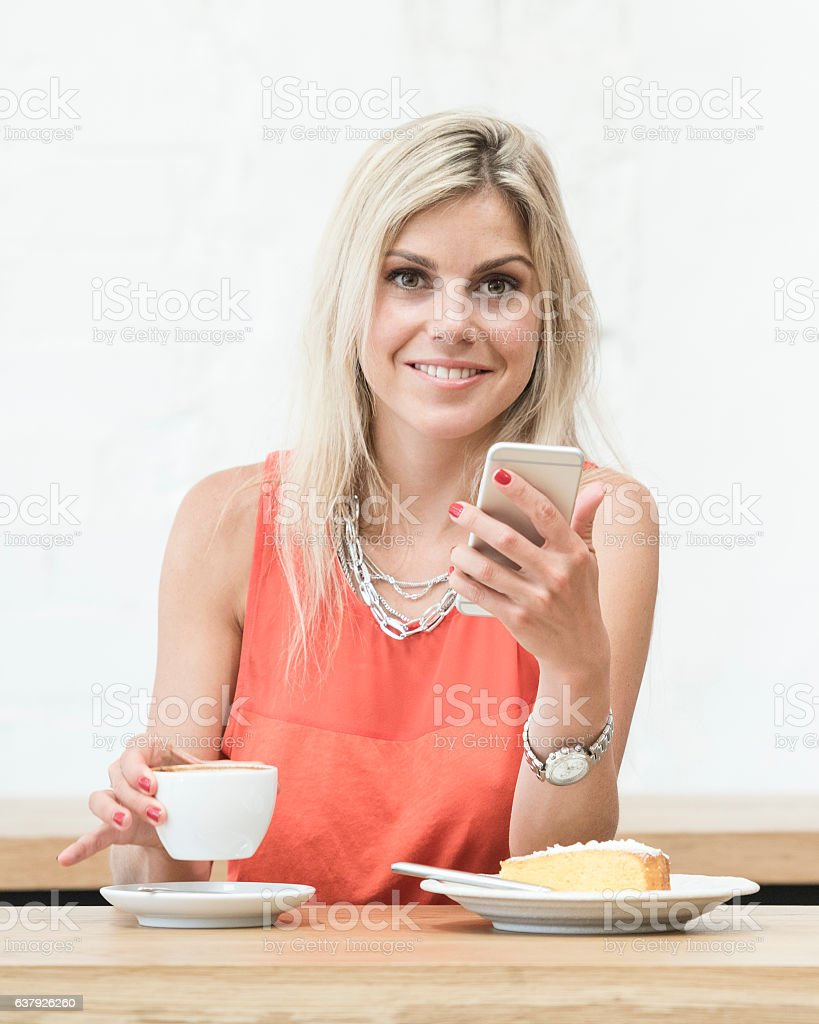 Portrait of young blonde woman holding cell phone and coffee - foto de stock