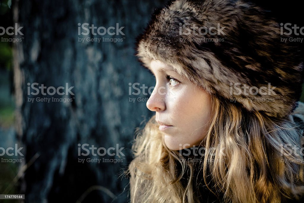 Portrait of Young blonde woman wearing fur hat, looking away stock photo