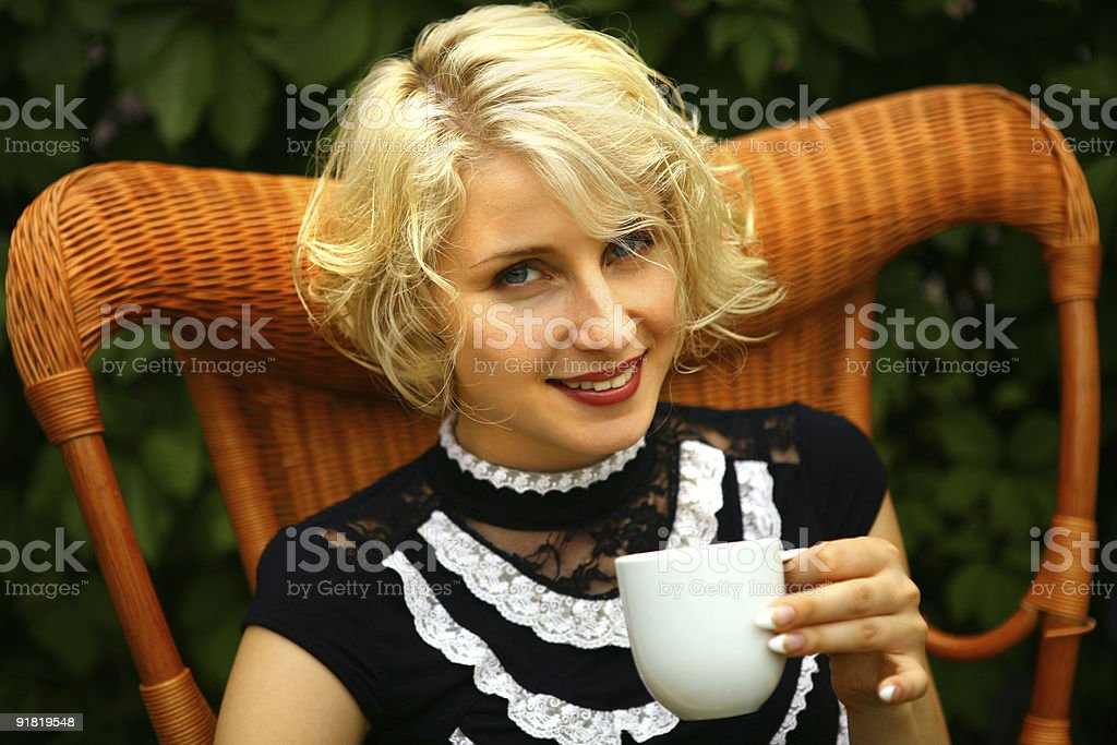 Portrait of young blonde woman with a cup  tea stock photo